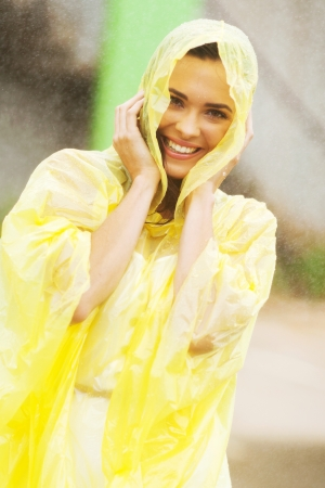 poncho: pretty woman dress in raincoat having fun in the rain Stock Photo