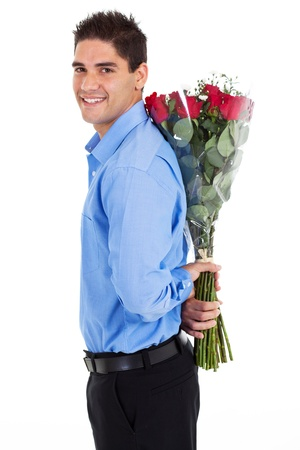gift behind back: young man hiding bunch of red roses behind his back Stock Photo