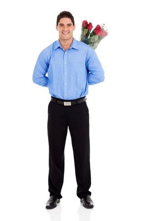 romantic young man hiding bunch of roses behind his back isolated photo