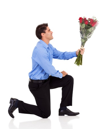 young man knee down on floor and giving bunch of roses isolated on white photo