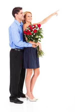 mujer con rosas: pareja feliz con el manojo de rosas aislados en blanco, la mujer est� se�alando