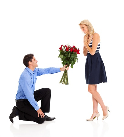 young man down on his knee to give bunch of roses to a woman photo