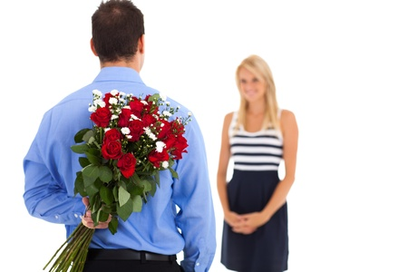 admirer: young man hiding bunch of roses behind his back to surprise his girlfriend on valentines day