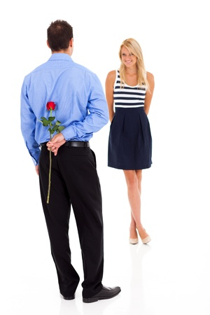gift behind back: romantic young man hiding rose behind his back