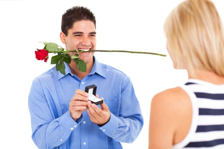 propose: young man with rose and ring proposing to his girlfriend Stock Photo