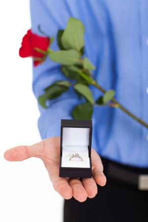 closeup of young man with engagement ring and rose photo
