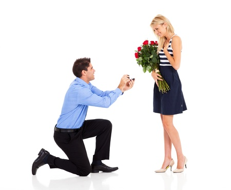 marriage proposal: young man down on his knee proposing to girlfriend
