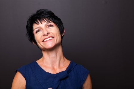 optimistic middle aged woman portrait on black background photo