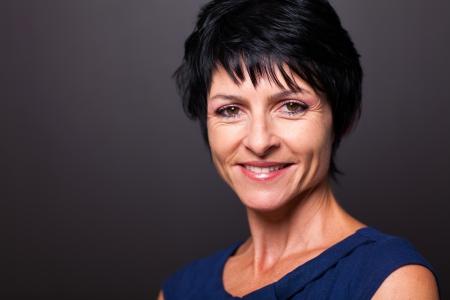 woman black background: pretty middle aged woman closeup portrait on black