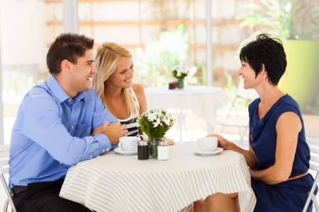 coffee shop: young woman with boyfriend meeting future mother in law in cafe Stock Photo