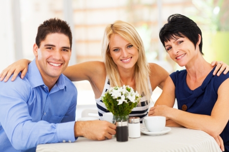 daughter in law: happy young man with wife and mother-in-law in cafe Stock Photo