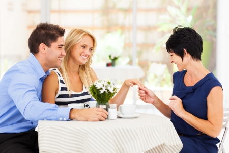 mother in law: happy young woman with fiance showing her engagement ring to her mother
