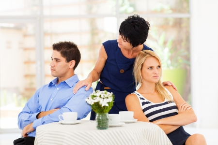 caring mother reconciling fighting young couple photo