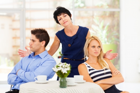 women fight: middle aged mother feeling helpless when caught in between young couples fight