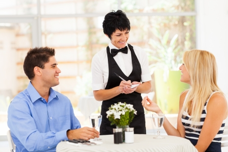 dining out: friendly middle aged waitress taking order from customer in restaurant