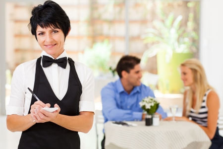 dining out: elegant mature waitress working in restaurant Stock Photo