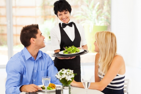 happy waitress serving customers in restaurant photo