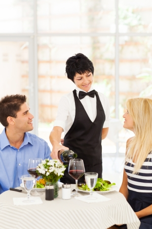 dining out: friendly mature waitress serving wine to diners in restaurant Stock Photo