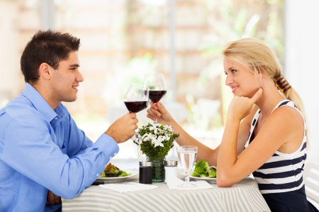blonde couple: young couple drinking wine in modern restaurant Stock Photo