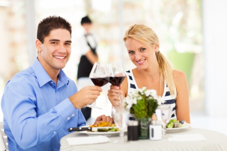 young couple drinking wine in restaurant photo