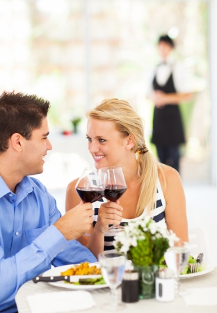 wine and dine: happy young couple eating out in restaurant Stock Photo
