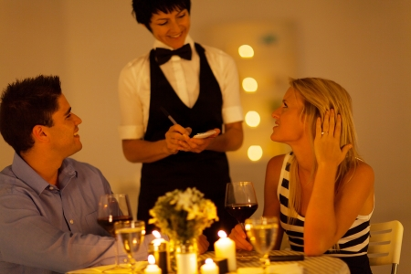 young couple place dinner order to waitress in a restaurant photo