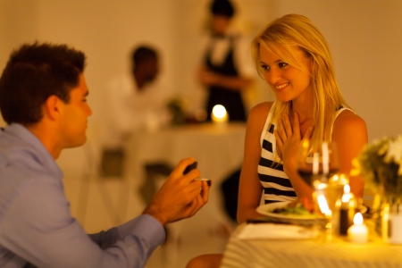 engagement: young man proposing to his girlfriend in a restaurant while having candlelight dinner Stock Photo