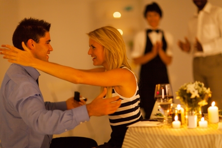 proposed: young woman hugging her boyfriend after he proposed in restaurant Stock Photo
