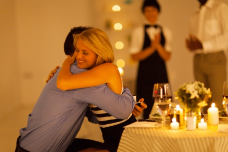 proposed: young woman hugging her boyfriend after he proposed in a restaurant