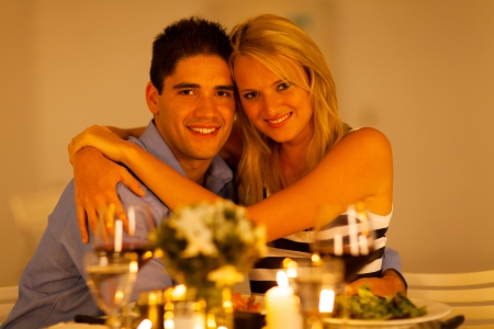loving young couple hugging in restaurant during dinner time photo