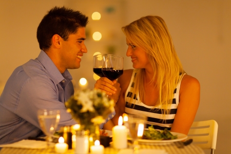 luz de velas: amante joven pareja disfrutando de una copa de vino en el restaurante Foto de archivo