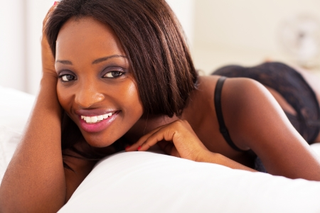 pretty african american woman lying on bed photo