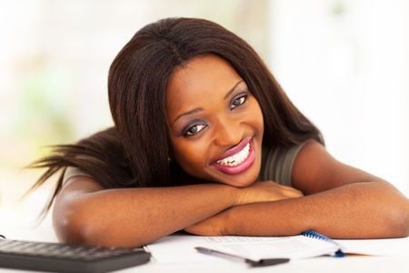 happy african american university student lying on desk photo