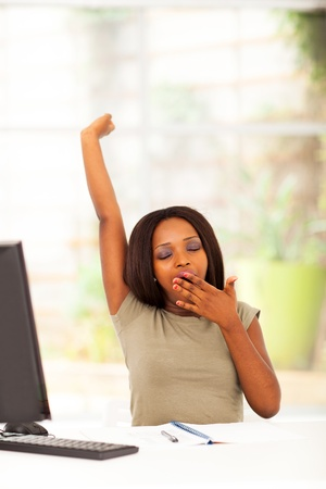 african american woman: young african american woman yawning in front of desk