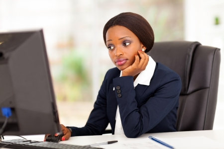 navy blue suit: thoughtful african american businesswoman looking at computer screen in office