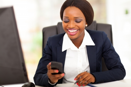 happy african american busniesswoman reading sms in office Stock Photo - 17457163