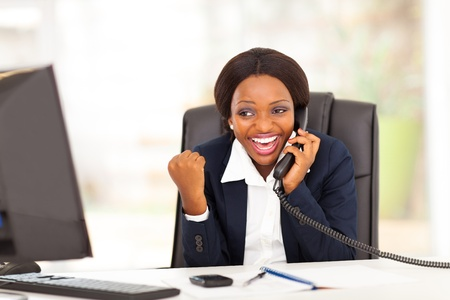 business woman phone: young african american businesswoman receiving excited news in office Stock Photo