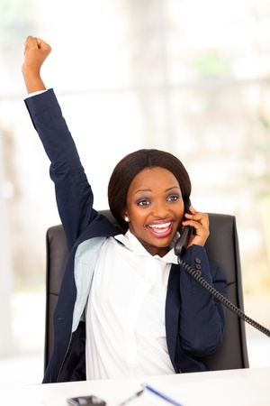 business woman phone: young african american businesswoman receiving exciting news Stock Photo