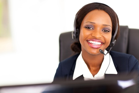 african business: happy african american telephonist in front of computer
