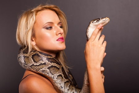 pretty young woman holding python  photo