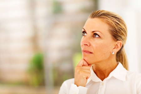 thoughtful senior businesswoman looking up photo