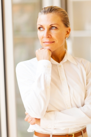 thoughtful female senior office worker looking outside window photo