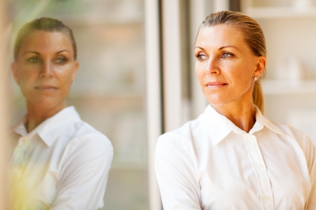 reflection: elegant middle aged businesswoman standing by office window Stock Photo