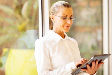 employee satisfaction: senior businesswoman using tablet computer in office