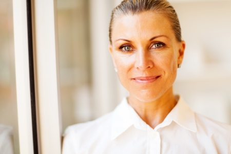 determination: elegant middle aged businesswoman closeup portrait in office Stock Photo