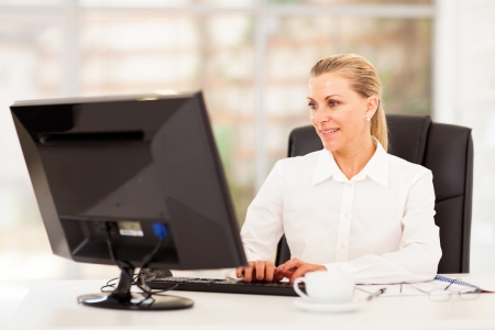 middle aged female office worker working on computer  photo