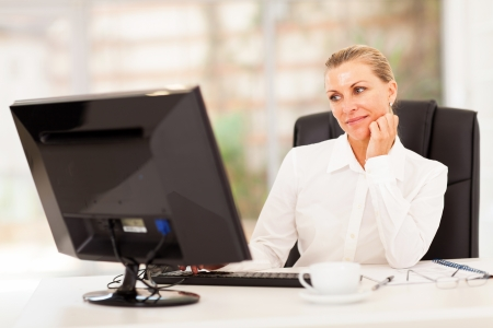 thoughtful senior businesswoman in front of computer photo