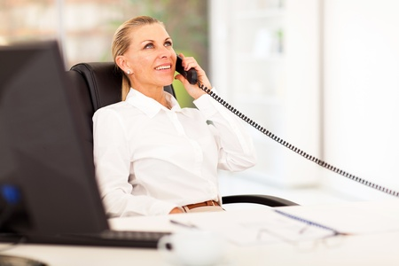 mid age businesswoman talking on the phone in office photo