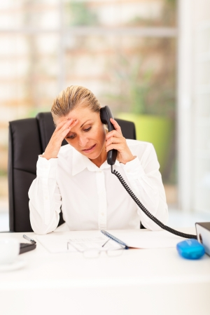 worried senior businesswoman talking on the phone in office photo