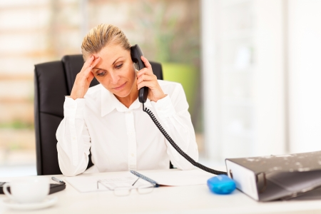 worried executive: serious middle aged businesswoman talking on phone